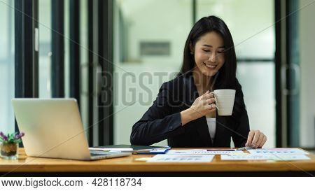 Adult Businesswoman Sitting And Drinking Coffee During Working At Office
