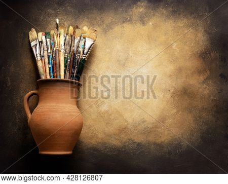 Paint brush in clay jug at  art painting canvas as abstract background texture. Paintbrush for painting for artistic paint still life. Abstract art concept