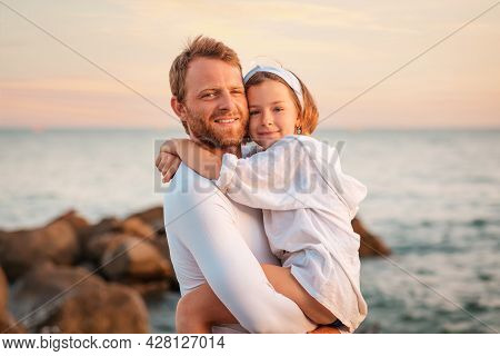 Father's Day. Portrait Of A Smiling Father Hugging His Preschool-age Daughter In His Arms. In The Ba