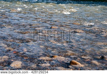Sun Glare On Surface Water And Smooth Stones At Bottom Stream, Background. Transparent Water In Rive