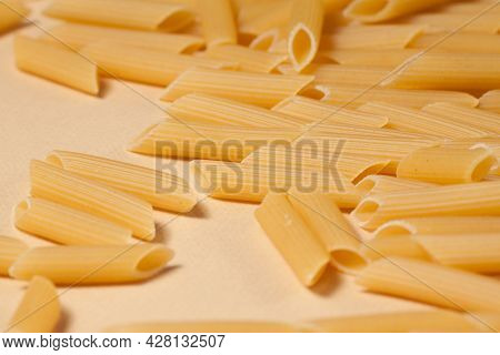 Penne Pasta Background. Pasta Penne Texture Background. Tube Like Macaroni. Heap Of Pasta.
