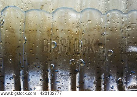 Drops Of Condensate Drain From A Cold Bottle Of Drinking Water On A Hot Day, Abstract Background Wit