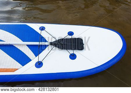 Sup Board, Paddle Board With A Paddle On The Background Of Water Close-up. Sup Boarding Equipment. W