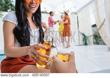 Smiling Brunette Woman Clinking Bottles Of Beer With Man Near Multiethnic Friends On Blurred Backgro