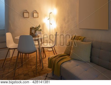 Modern living room of a mountain house with a table, four designer chairs and a comfortable sofa with a blanket. Nobody inside