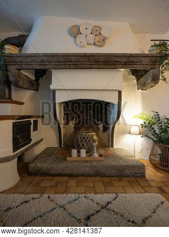 Front view of a fireplace in the living room of a mountain house. Tiles and a carpet on the floor. Nobody inside