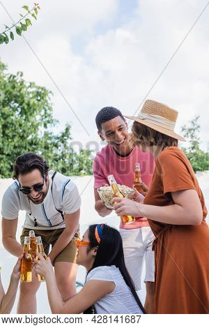Excited African American Man Holding Popcorn Near Multiethnic Friends Clinking Bottles Of Beer