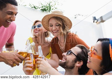 Pleased Multicultural Friends Clinking Bottles Of Beer During Summer Party Outdoors