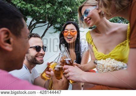 Excited Multicultural Friends Clinking Bottles Of Beer During Party On Blurred Foreground
