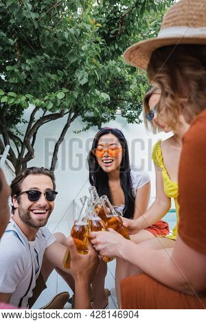 Excited Multiethnic Friends Clinking With Bottles Of Beer Near Green Tree In Patio