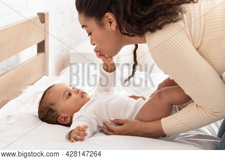 African Mommy Kissing Babys Hand Waking Up After Sleep Indoor