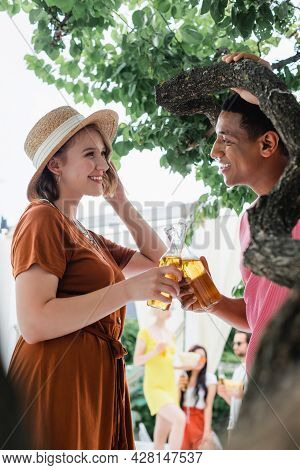 African American Man And Smiling Woman In Straw Hat Clinking Bottles Of Beer Near Blurred Friends