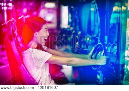 Japanese gaming cyber cafe girl gamer having fun gaming. Driving racing car game fun Asian woman playing videogame virtual sports cars arcade machine.