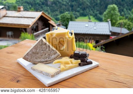 Cheese Collection, Swiss Cow Cheese Emmental, Tomme And Dark Chocolate And Mountains Village In Apls