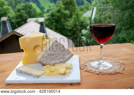 Cheese Collection, Swiss Cow Cheese Emmental, Tomme, Glass Of Red Wine From Savoie And Mountains Vil