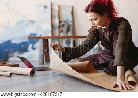 Young woman artist sitting on a floor of an art studio unrolling parchment paper