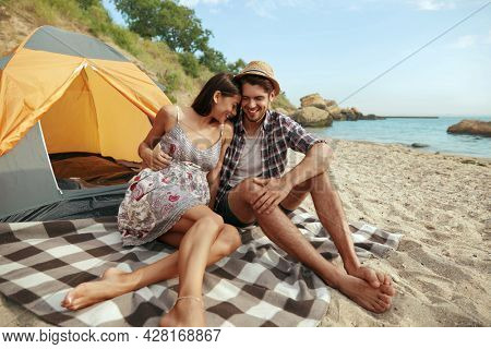 Happy guy embracing his pleased girl on sandy sea beach. Young european couple in love resting. Concept of romantic relationship and enjoying time together. Camping vacation at summertime. Sunny day