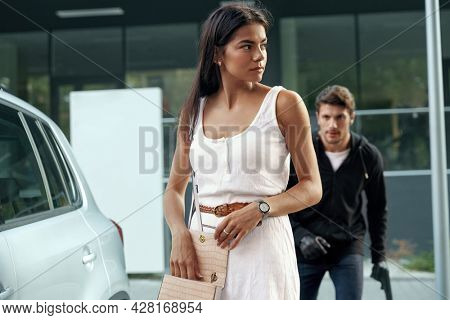 European girl stand near car while robber sneaking behind. Brunette young lady search something in her handbag. Male bandit wear hoodie and hold pistol. Concept of robbery and kidnapping. City daytime