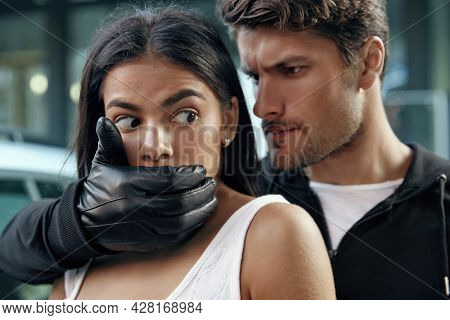 Angry robber closing mouth and threatening with pistol to frightened girl. Young brunette woman wear white dress. European male bandit wear hoodie. Close up view. Concept of robbery and kidnapping