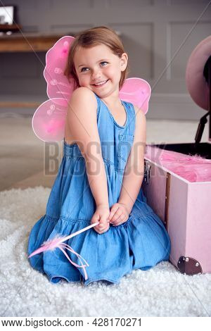 Young Girl Wearing Fairy Wings Having Fun Playing With Dressing Up Box At Home