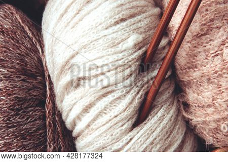 Skeins Of Yarn In Beige And Brown Colors And Knitting Needles On A White Background. Craft On White