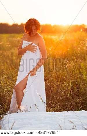 Charming Caucasian Woman 30-35 Years Old In A Field At Sunset In Summer