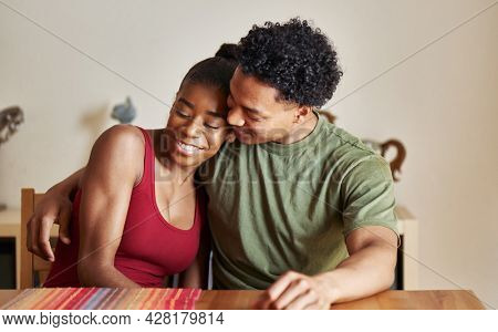 loving african american couple hugging at table