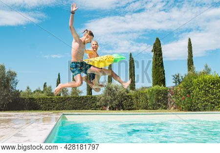 Laughing Son With Father In The Inflatable Ring Having Fun On A Merry Vacation. Cheerful Fooling Aro