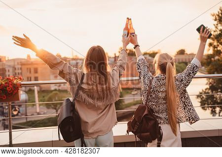 Girls With Their Hands Raised Stand With Their Backs On The Roof And Clink Bottles At Sunset