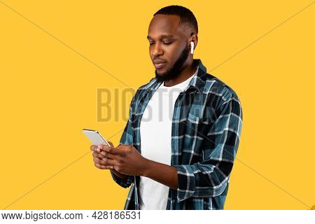 Black Millennial Male Using Cellphone Wearing Earbuds On Yellow Background