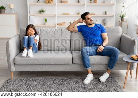 Father Sitting Separate On Couch With Offended Crying Daughter