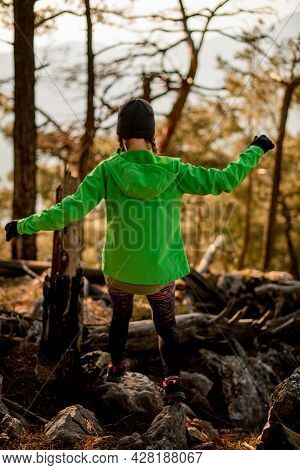 Back View Of Woman With Outstretched Arms To Sides Against Trees In Forest