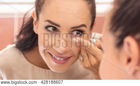 A Young Woman Puts Contact Lenses In Her Eyes In The Morning In The Bathroom In Front Of A Mirror.
