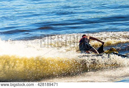A Man Rides A Jet Ski From Under Which Water Splashes Fly In Different Directions On A Sunny Summer