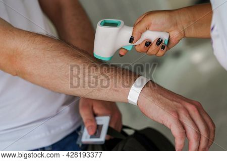 Female Doctor Checking Temperature Using Infrared Thermometer. Closeup Of Doctor With Contactless In