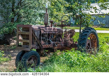 Old Rusted Farm Tractor Left For Scrap In A Farm Field In Tall Weeds With A Couple Of Farm Buildings
