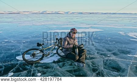 Man Sitting Near Her Bike On Ice. Athlete Cyclist Stopped To Res