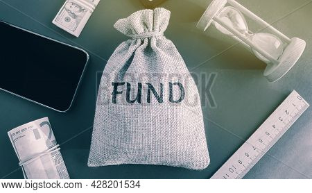 A Bag With Money And The Word Fund. The Concept Of Providing Financial Resources To Organizations An