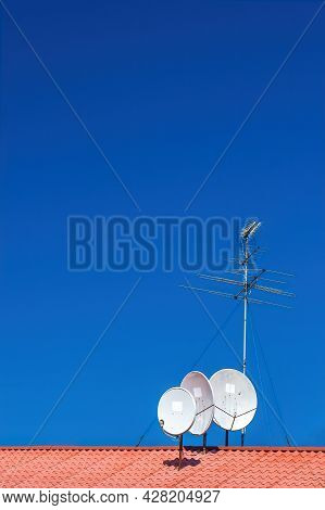 Four Antennas On The Roof Of A  House, Parabolic Satellite Dishes, Long-wave, Medium-frequency Radio