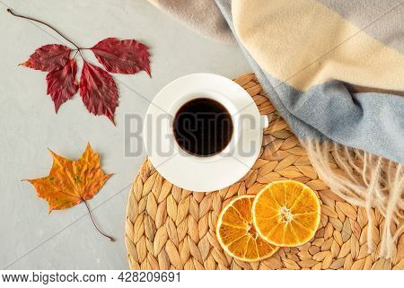 Cup Of Black Coffee On A Gray Background With Autumn Leaves, A Warm Stole, A Wicker Napkin And Slice