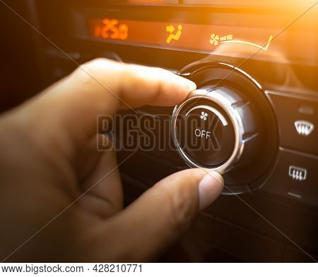 A Hand Is Adjusting Level Temperature Control Button Of Air Condition On Dashboard In The Cockpit Of