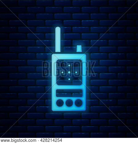Glowing Neon Walkie Talkie Icon Isolated On Brick Wall Background. Portable Radio Transmitter Icon.