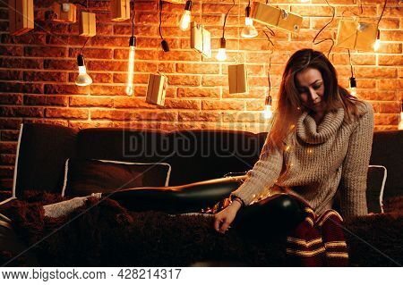 Nice Woman Sitting On Couch And Look Down. Christmas Atmosphere. New Year Mood. Light Bulbs And Pres