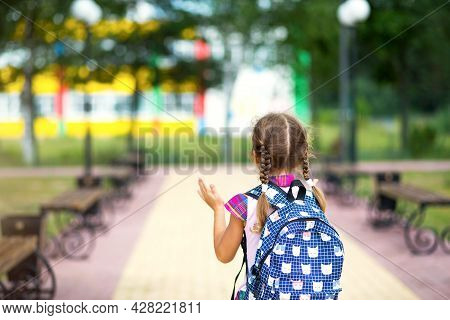 Cheerful Girl With A Backpack And In A School Uniform In The School Yard Back To The Frame. Back To