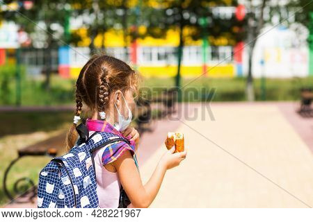 Girl With A Backpack Take Off The Medical Mask And Eating A Pie Near The School. A Quick Snack With
