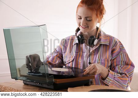 Beautiful Young Woman Using Turntable At Home