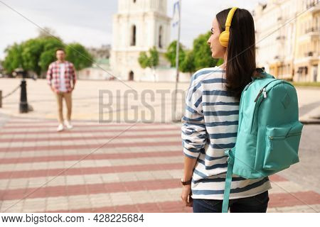 Young Woman With Headphones Waiting To Cross Street. Traffic Rules And Regulations