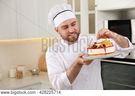 Happy Professional Confectioner Decorating Delicious Cake In Kitchen