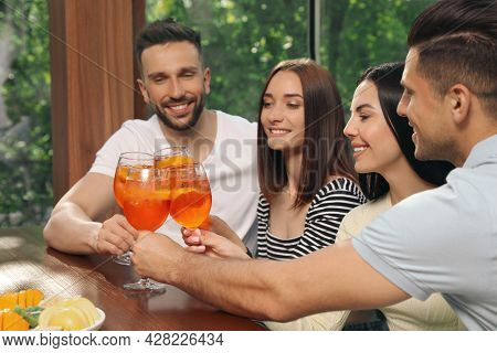 Friends Clinking Glasses Of Aperol Spritz Cocktails At Table