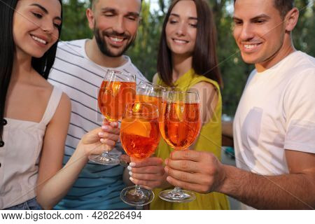 Friends Clinking Glasses Of Aperol Spritz Cocktails Outdoors